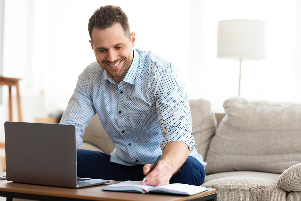 man using laptop at home and writing notes 53VA6FT