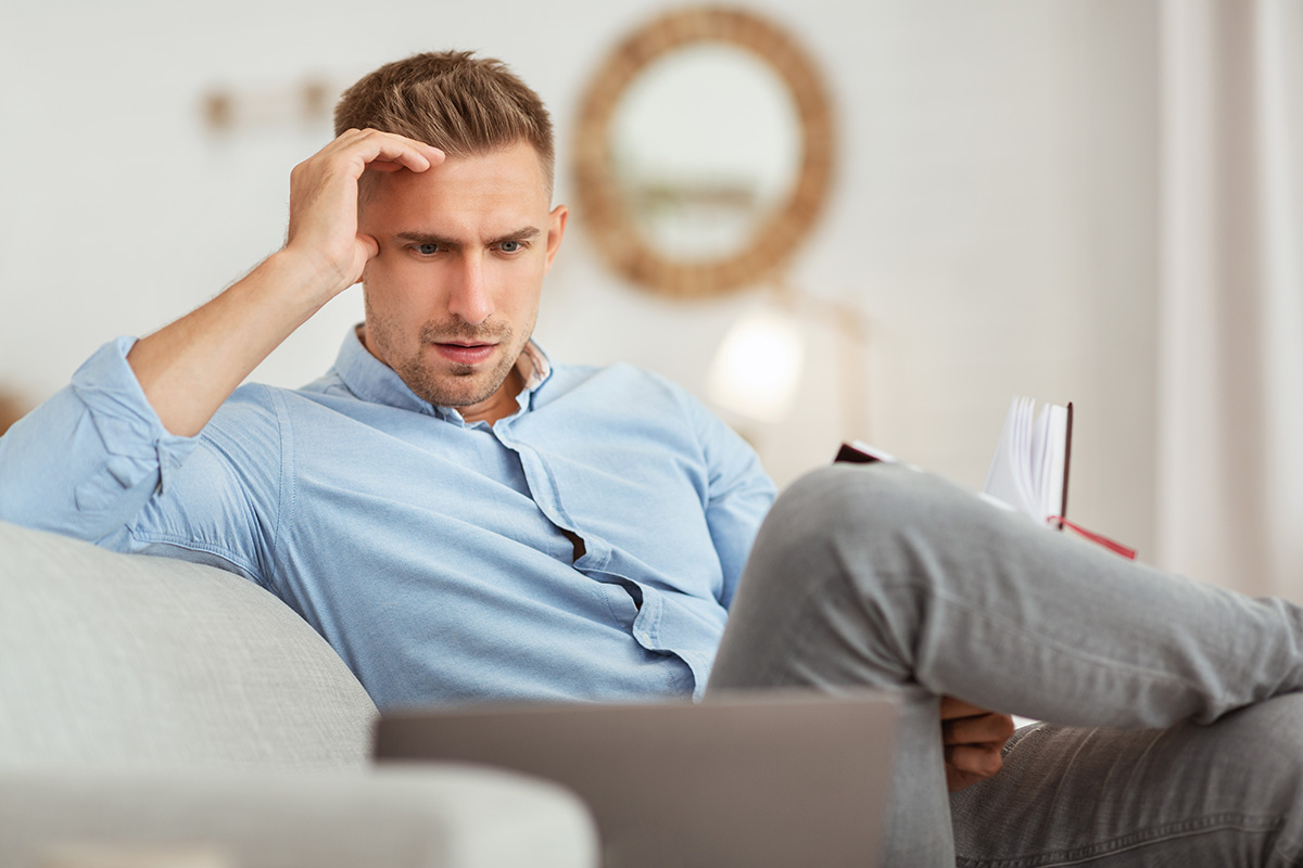 portrait of pensive man sitting on couch using pc 6KC6K8J 1